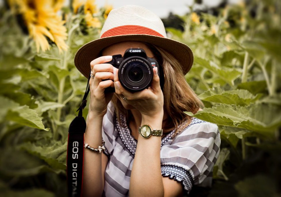 selective-focus-photography-of-woman-holding-dslr-camera-1264210